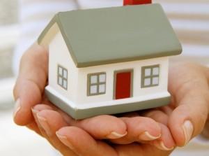 Mujer con una casa en las manos